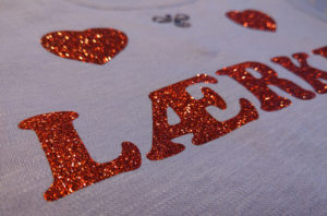Tryk på tøj med glimmer. Tøj og arbejdstøj med tryk og print